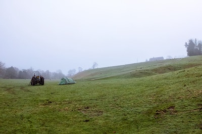 Our small tent in a large misty field with a tractor