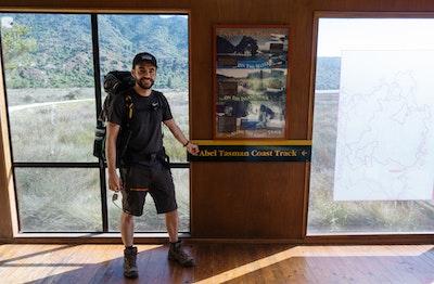 Jamie McHale standing in front of the Abel Tasman Coastal Track sign
