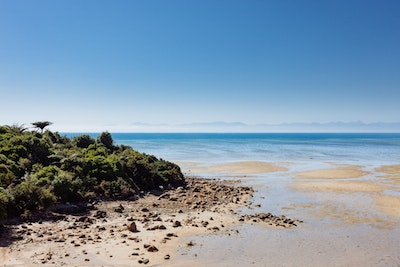 A view over a golden beach with blue mountains visible across the Tasman Bay