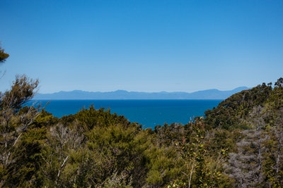A view over a sandy inlet with the Tasman Bay in the background