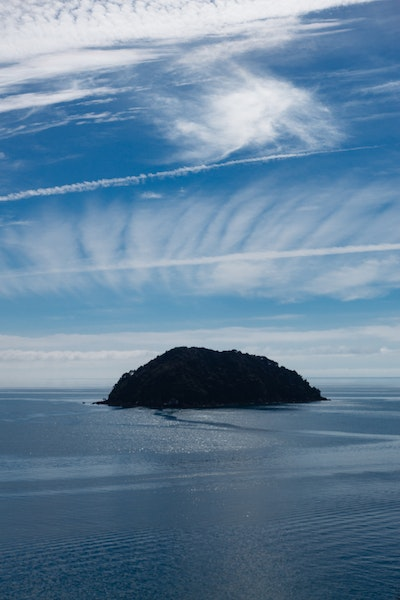 Clouds and plane trails over a small dark island