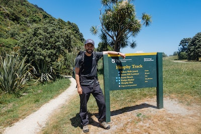 Me standing next to a Heaphy Track sign, having finished the walk
