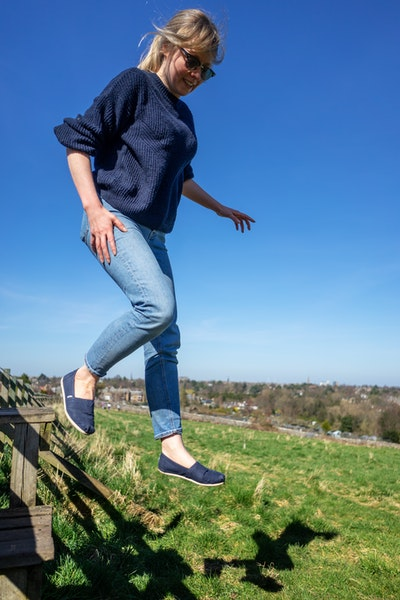 Harriet jumping off a fence in a field